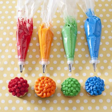 4 pastry bags, different colored frosting, different tips; 4 decorated cupcakes