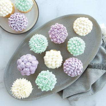 Cupcakes on a platter and plate, showcasing frosting designs using tips from set.