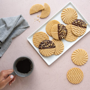 Plain and chocolate dipped geo stamped cookies on a plate, hand holding coffee.