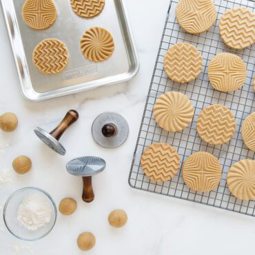 Baked geo cookies on cooling rack, stamped dough on sheet pan, stamps on surface