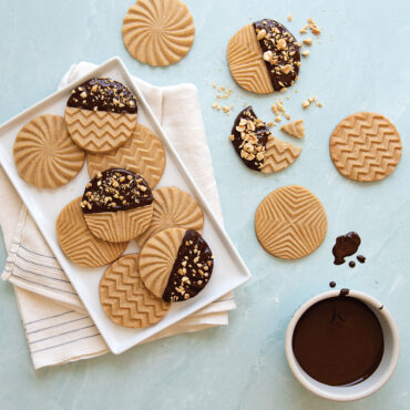 Plain and chocolate dipped geo stamped cookies on a plate and on surface.