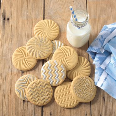 Baked Geo stamped sugar cookies with 3 designs, milk on table