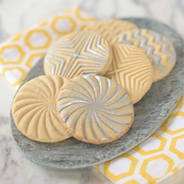 6 baked stamped sugar cookies with edible silver decorations on plate