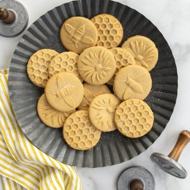 Baked honeybee stamped sugar cookies on metal plate, cookie stamps around plate