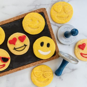 Decorated and plain baked emoji stamped cookies with cookie stamps