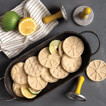 Baked citrus cookies in a tray with stamps and limes/lemons on surface