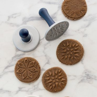 Unbaked stamped cookies on counter with two stamps showing wood handles on stamps
