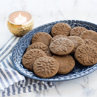 Baked gingerbread stamped cookies on plate