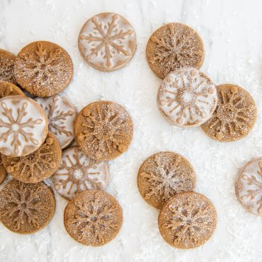Baked stamped gingerbread cookies with snowflake cookie stamps, dusted in sugar