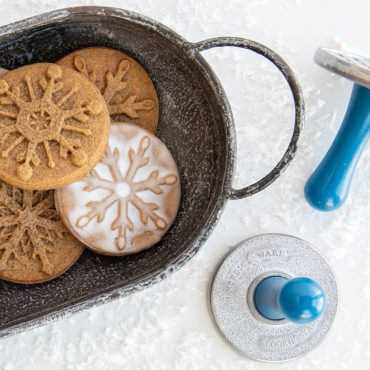 Closeup of stamped snowflake cookie stamps, in tray with stamps on surface