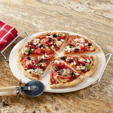 Baked pizza on stone, cut into wedges, with pizza cutter