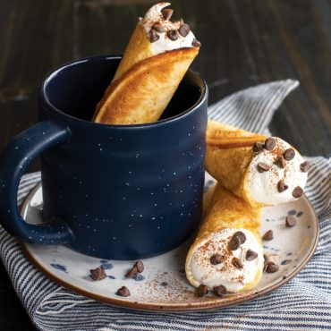 Filled krumkake with cream, chocolate chips and cocoa powder, one in mug and two on a plate