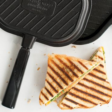 Grill press with grilled cheese sandwich wedges