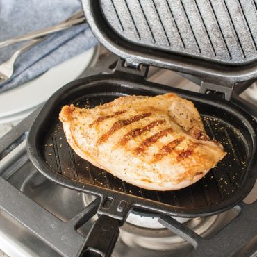 Open grill press with grilled chicken breast