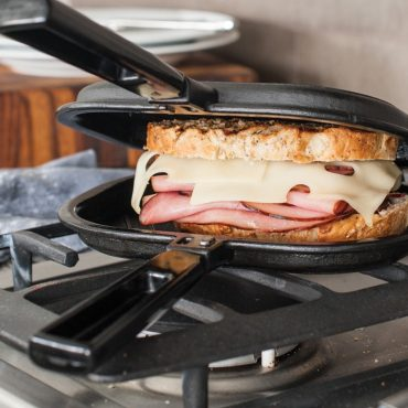 Grill press on stovetop with ham and cheese grilled sandwich