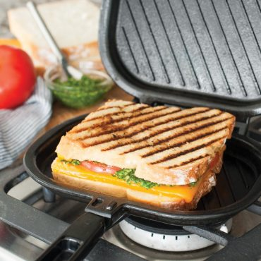 Open grill press on stovetop with grilled sandwich