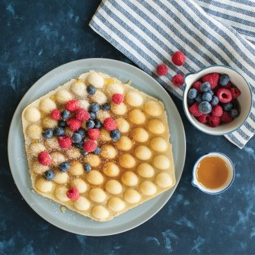 Cooked bubble waffle on plate with fruit