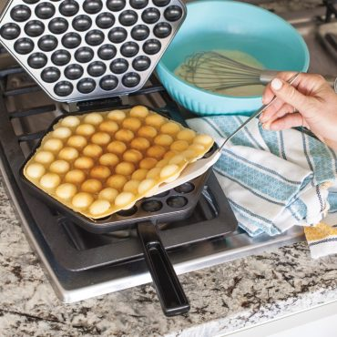 Open waffler with cooked puff waffle on stovetop
