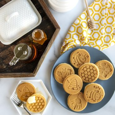Plated cooked bee themed pancakes with butter container, syrup, honey