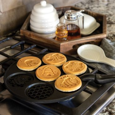 Bee Pancake Pan on stovetop with 5 cooked pancakes in cavities, syrup and butter on the side counter