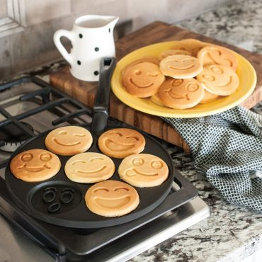 Pancake pan on stovetop with cooked smiley face pancakes
