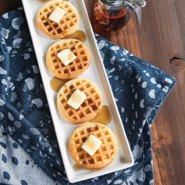 Cooked mini waffles with syrup and butter on plate