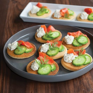 Pancakes on platter with savory topping of smoked salmon, cucumber, dill and cream cheese