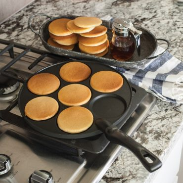 Cooked plain pancakes on pancake pan on stovetop, stack of pancakes on plate on counter.