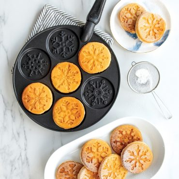 Pancakes on snowflake pan, plate filled with snowflake pancakes with powdered sugar on top