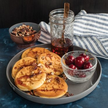 Plate with pancakes, syrup, nuts, fresh cherries