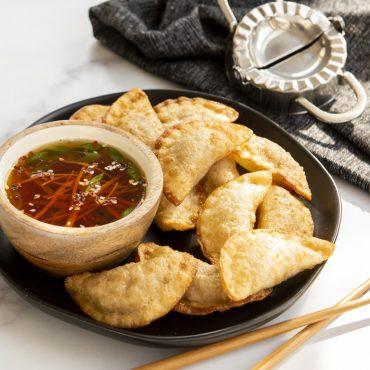 Homemade dumplings with dipping sauce on a plate, dumpling maker next to plate.