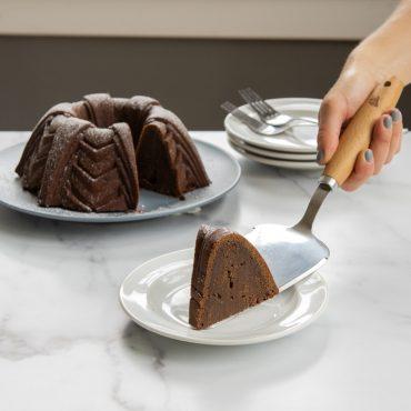 Hand serving slice of chocolate Bundt cake on plate using caker server, cut baked Bundt in background.