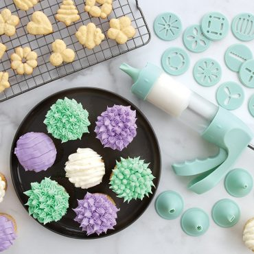 Decorated cupcakes and baked spritz cookies using discs and frosting tips in set