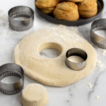 Biscuit dough on floured surface cut out with one biscuit cutter, other biscuit cutters on surface and baked biscuits on platter in background.