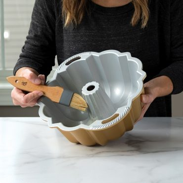 Prepping Anniversary Bundt Pan with Pastry Brush and baking spray.