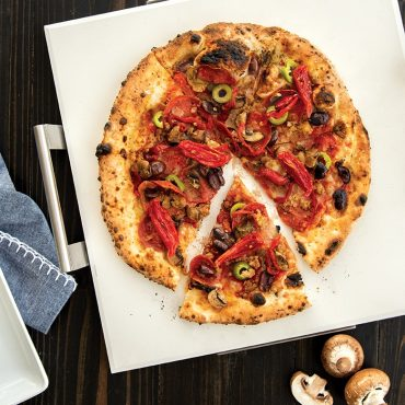 Baked pizza on square pizza stone