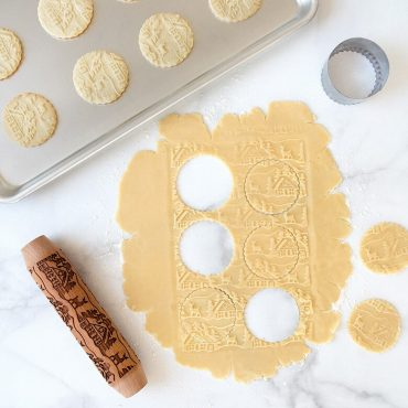 Rolled out dough with embossed rolling pin, round cut outs made in dough, pan of baked embossed cookies in background.