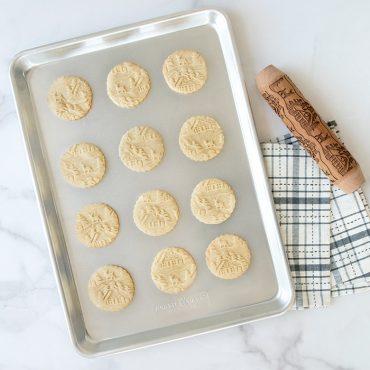 Baked embossed cookies on half sheet, embossed rolling pin next to pan