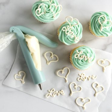 """Cupcakes with heart decorations and """"Love"""" spelled out with white frosting using Deco Pen, Deco pen next to cupcakes filled with white frosting."""