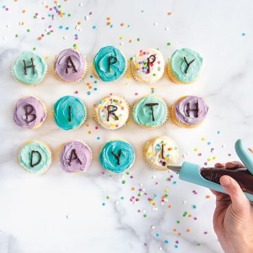 """Cupcakes in different colors spelling out """"Happy Birthday"""" using Deco Pen, sprinkles on surface"""