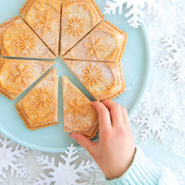 Baked shortbread made in Disney Frozen 2 Snowflake Shortbread Pan dusted with powdered sugar, kid's hand taking a slice
