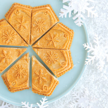 Baked shortbread made in Disney Frozen 2 Snowflake Shortbread Pan, on blue plate with cut pieces