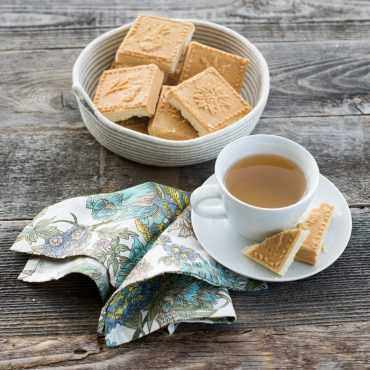 Baked shortbread squares in bowl, cup of tea