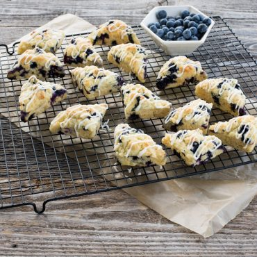 Baked mini blueberry scones on cooling rack