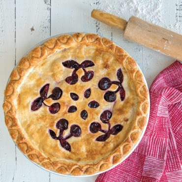 baked cherry pie with cherry design crust, rolling pin