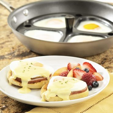 Poacher in saute pan with poached eggs, Eggs Benedict on plate with fresh fruit