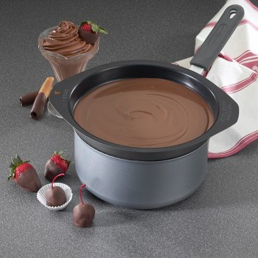 Double boiler in sauce pan with melted chocolate, chocolate dipped strawberries on plate