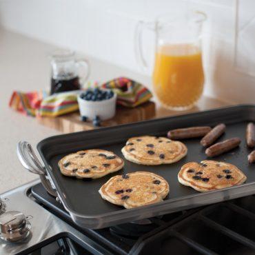Griddle on stovetop, pancakes, sausage on griddle