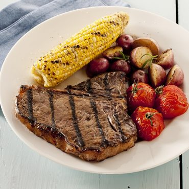 steak, corn on the cob, roasted tomatoes and potatoes on plate