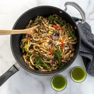 Sir fry noodles, veggies, and beef cooked in Big Bowl Wok with two cups of green tea on surface.